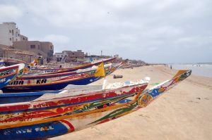A row of Senegal canoes along the shore of the beach.